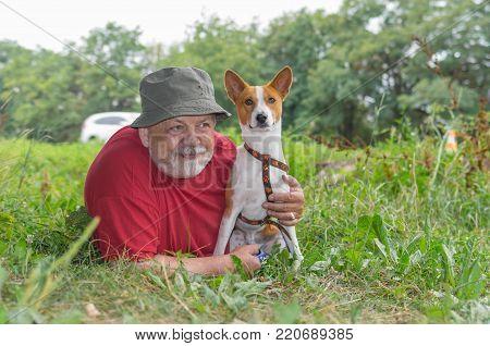 Senior man with Basenji dog lying in the grass at summer morning (shallow dof)