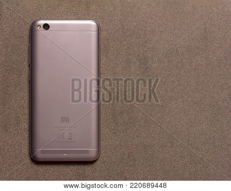 Chinese smartphone Xiaomi Redmi 5A silver back side close up view from above on grey background with copy space