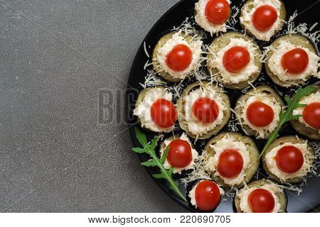Fried eggplant with cheese, tomatoes, garlic, served on a plate, black background. View from above
