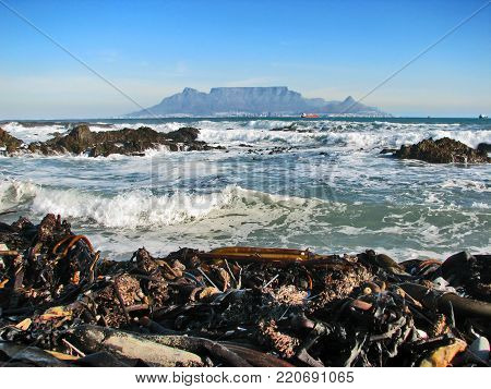 FROM BLOUBERG STRAND, CAPE TOWN, SOUTH AFRICA, WITH A ROUGH SEA IN THE FORE GROUND AND A VIEW OF TABLE MOUNTAIN IN THE BACK GROUND