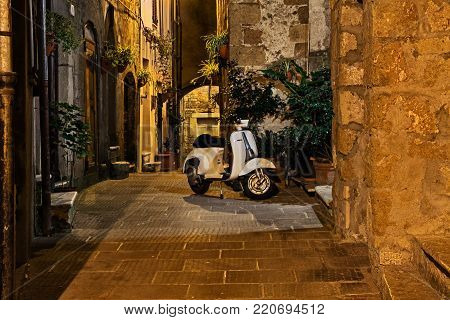 Pitigliano, Tuscany, Italy - September 30, 2016: alley at night in the old town with a vintage Italian scooter Vespa. Photo taken on September 30, 2016 in Pitigliano, Grosseto, Tuscany, Italy