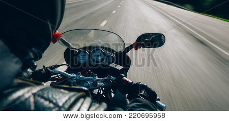 Motobiker, motorbike and road. Sunny summer day, speed, digital speedometer.