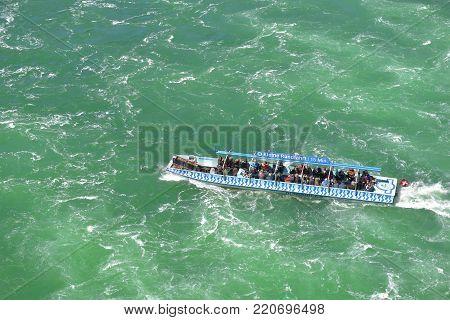 Rhein waterfall, Germany - April 2017: touristic boat, taking people on a cruise in Rheinfall basin