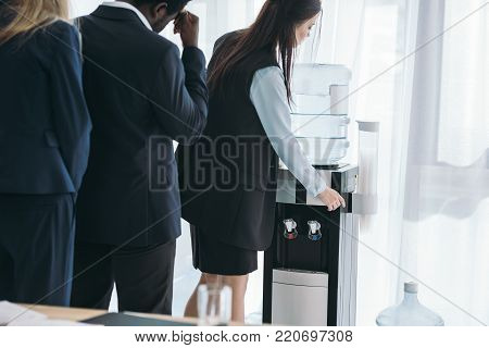 businesspeople standing in queue for water dispenser at office