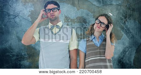 Geeky hipster couple thinking with hand on temple against rusty weathered wall