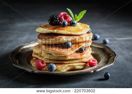Closeup of american pancakes with maple syrup on dark table