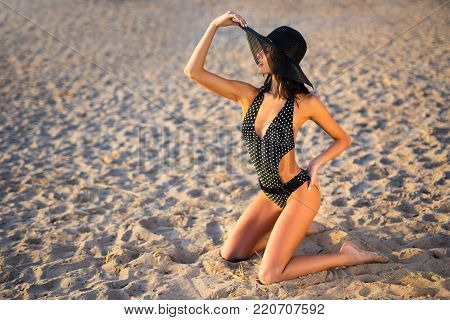 Sexy Beautiful Woman In Swimsuit And Hat Posing On The Beach