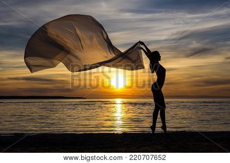 summer background - silhouette of slim sexy girl in bikini posing with scarf on the beach at sunset