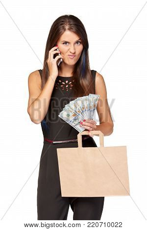 Woman holding paper shopping bag with blank copy space for text and cash US dollars talking on mobile phone making funny face, over white background