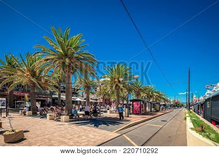 Glenelg, South Australia - February 28, 2016: People relaxing at Moseley Square in Glenelg on a bright summer day viewed towards tram line