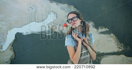 Geeky hipster woman holding rose  against rusty weathered wall