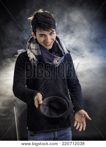 Cheerful young man posing and begging with hat in studio.