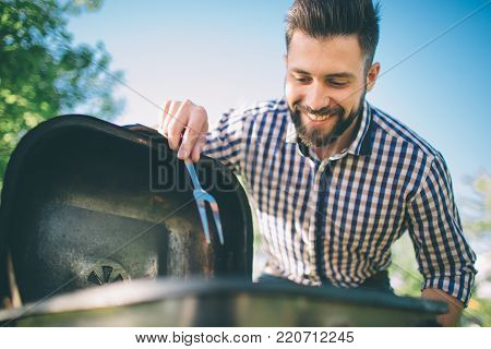 Handsome man preparing barbecue for friends. man cooking meat on barbecue - Chef putting some sausages and pepperoni on grill in park outdoor - Concept of eating outdoor during summer time