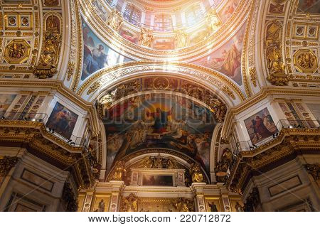 ST PETERSBURG, RUSSIA - AUGUST 15, 2017. Ceiling decorated with sculptures and Bible paintings. Interior of St Isaac Cathedral in St Petersburg, Russia. Inside view of St Petersburg Russia landmark