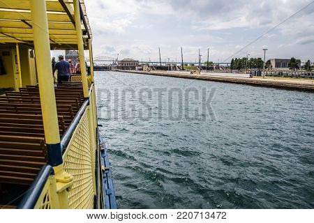 Sault Ste Marie, Michigan, USA - August 9, 2015: Tour boat carries tourists into the world famous Soo Locks. The Soo Locks Boat Tour takes visitors through the Locks along the waterfront district of Sault Ste Marie Michigan and Ontario.
