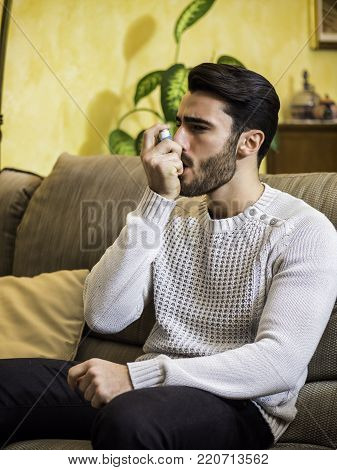 Handsome young man using inhaler for asthma, while sitting on sofa at home.