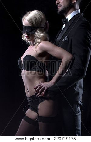 Stylish man touching sexy blonde lover in blindfold closeup, sensuality and foreplay