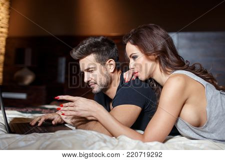 Young caucasian couple online shopping by laptop on bed