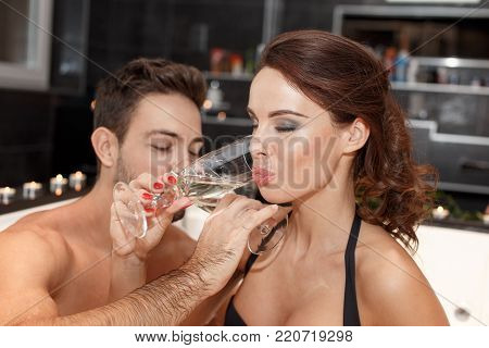 Young couple drinking champagne in jacuzzi, honeymoon poster