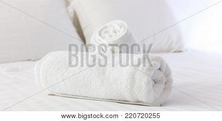 Hotel Bedroom. White Fluffy, Folded Towels, Linen Sheets And Pillows On Bed. Close Up View.