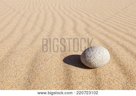 White round stone lying on clean sand. Concept of balance, harmony and meditation. Minimalism. Minimal rock Zen background