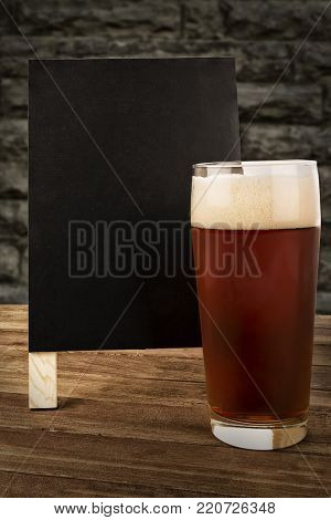 Glass of beer and blackboard disposed on a bar of a restaurant.