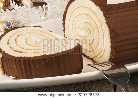 Chocolate yule log cake with Christmas decorations disposed on wooden table. Really close up.