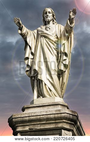 Jesus Christ statue with light flare near of his head.