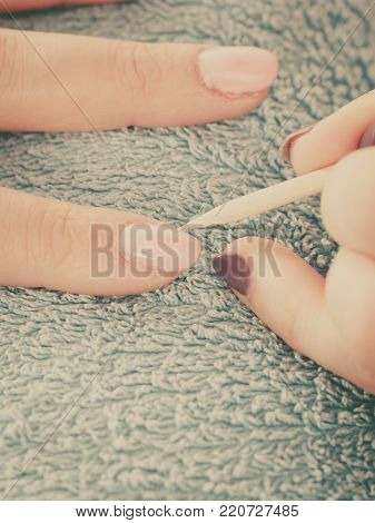 Nail care, beauty wellness spa treatment concept. Woman beautician preparing nails before manicure, pushing back cuticles using wooden stick