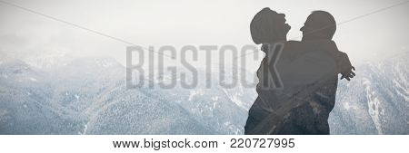 Mature couple hugging and having fun against beautiful mountain range in ski resort