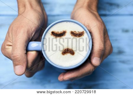 high-angle shot of a young caucasian man with a blue cup of cappuccino with a sad face drawn with cocoa powder on the milk foam, on a blue rustic table
