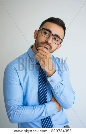 Closeup portrait of thoughtful young business man looking away and touching chin. Contemplation concept. Isolated front view on grey background.