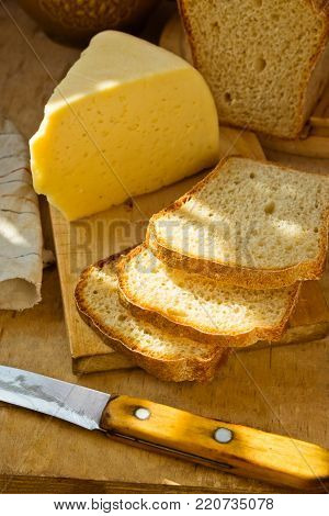 Loaf of Sourdough Bread Sliced on Wood Cutting Board Chunk of Cheese Knife Linen Towel. Golden Sunlight Flecks Rustic Kitchen Interior. Cozy Atmosphere