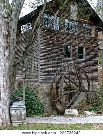 a neglected and abandoned old gristmill with a collapsing waterwheel