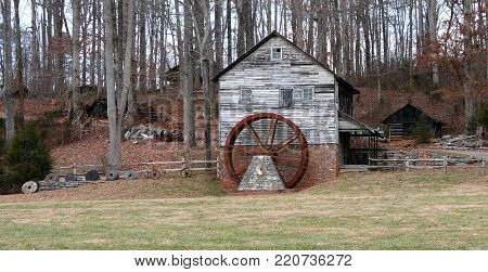 an old gristmill with a rusty wheel near the woods