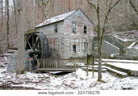 an old gristmill in a light dusting of snow