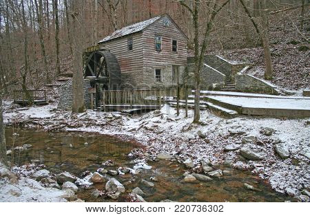an old gristmill beside a small stream, with a light dusting of snow