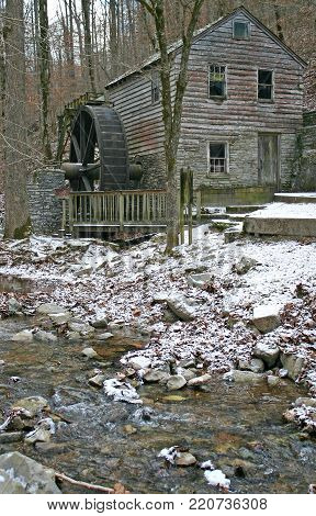 an old gristmill beside a stream, in light snow