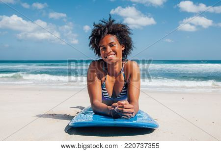 Surfer girl with afro hairstyle smiling, lying down on blue surfboard on the white sand at Dreamland beach, Bali, Indonesia