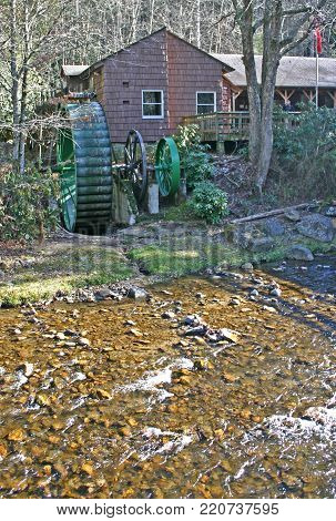 a gristmill with a green metal wheel beside a stream