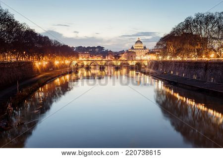 The bridge of Sant'Angelo, the Tiber river and in the background the Basilica of San Pietro, in a panoramic photograph at the sunset.