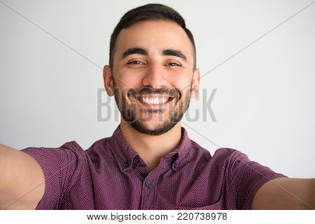 Closeup portrait of smiling young handsome man looking at camera and taking selfie photo on gadget which is out of view. Selfie concept. Isolated front view on white background.