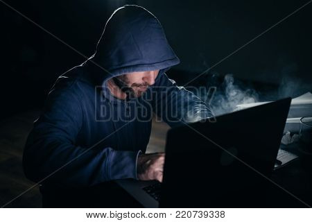an adult dangerous bearded man in a hood doing something illegal on a laptop, hacking in the dark