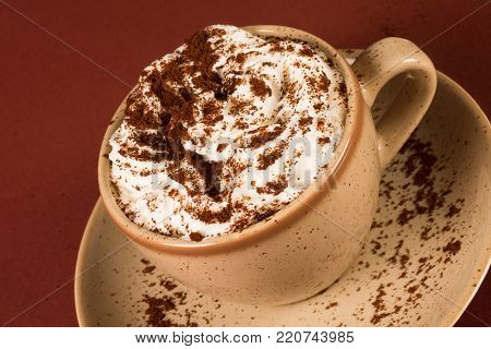 The cup of coffee or cappuccino with whipped cream is on red background.