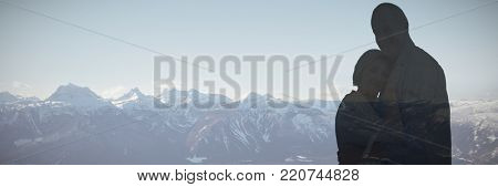 Happy mature couple hugging and smiling against three skiers relaxing on snow landscape
