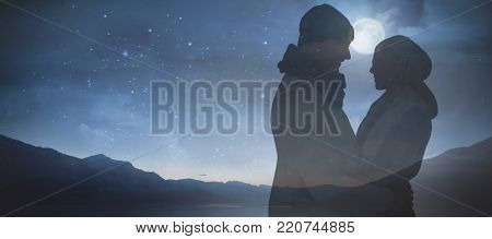 Happy husband holding wife while looking at each other against scenic view of lake against clear blue sky