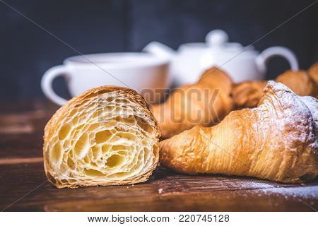 A cut croissant and a croissant with sugar powder lie side by side. A close-up of a cut croissant on the table. Beautiful croissant on the table beside the dishes and pastries. A white cup and a teapot stand in the background. Croissant close-up on a blue