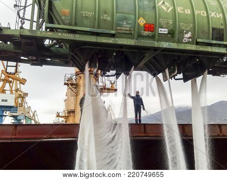 Novorossiysk, Russia - August 11, 2017: spillage of saltpeter from the car into the hold of the tanker. Loading of mineral fertilizers in the ship's hold.