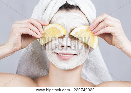 beauty woman getting facial mask. Attractive young woman with fruit mask on face at spa salon