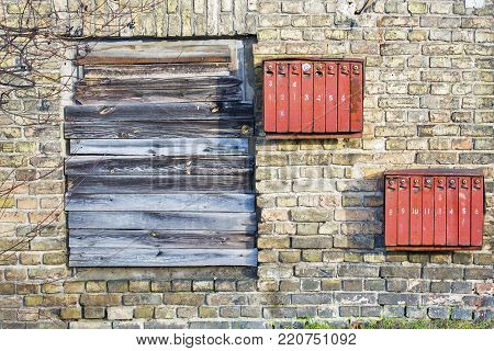 Rusty mailboxes on the brick grunge wall, boarded up window